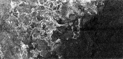 Pobřeží měsíce Titan– vlevo světlá pevnina azátoky, vpravo tmavé moře