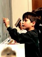 Žák píšící na tabuli - výuka soukromé školy